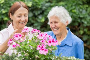 Senior woman and caregiver admiring flowers