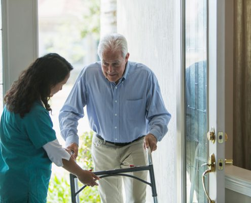 Elderly man with walker entering house